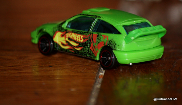 bright green hot wheels car on a wooden table