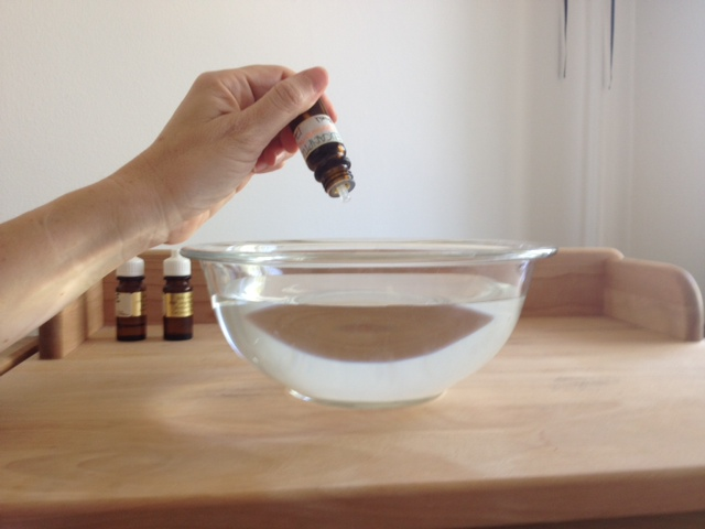 Dropping essential oils in water for sinus congestion steam inhalation
